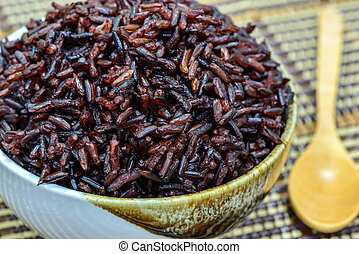 Close up rice berry in bowl with wooden spoon.
