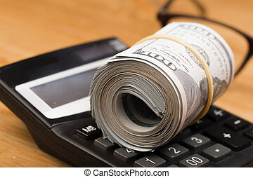 Close-up rolled American dollars banknotes with calculator ang glasses.