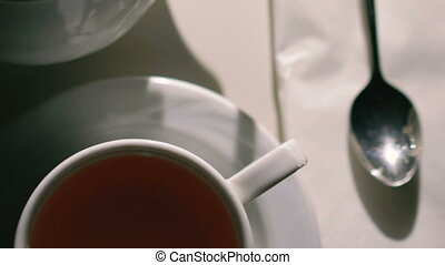 Close up rotating white background with cup of tea, spoon and teapot