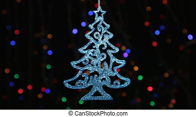 Close-up, rotation of a blue Christmas tree hanging on a silver rope. Christmas and New Year decoration.