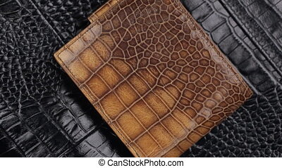 Close-up. Rotation of beautiful male wallet lying on a black...