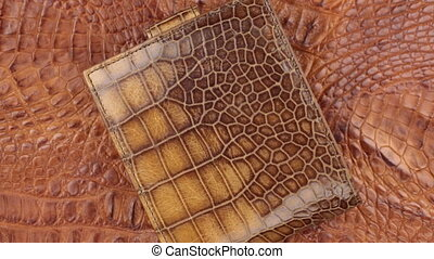 Close-up. Rotation of beautiful male wallet lying on a brown...