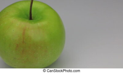 Close-up rotation of green apple, on a white background