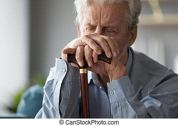 Close up sad older man holding hands on walking stick