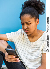 Close up sad young african american girl looking at cellphone