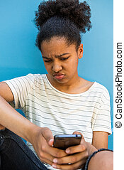 Close up sad young african american girl looking at mobile phone