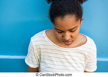 Close up sad young african american girl looking down