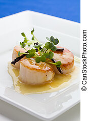 Close up Scallop seafood appetizer with vanilla stick and sauce.
