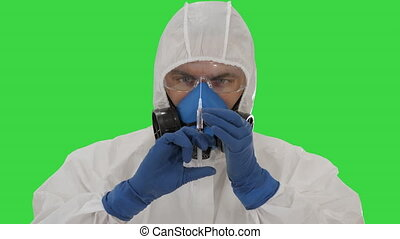 Scientist in protective gear holding syringe with injection on a Green Screen, Chroma Key.