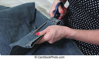 Close up seamstress cutting fabric With Scissors