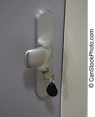 close up security key with chip in lock in modern silver apartment doors