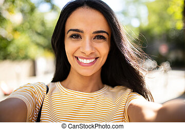 Close up selfie smiling North African young woman outside