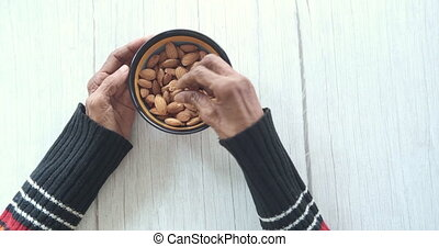 close up senior women hand holding a bowl on almond .