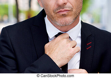 Close up serious businessman adjusting knot on tie