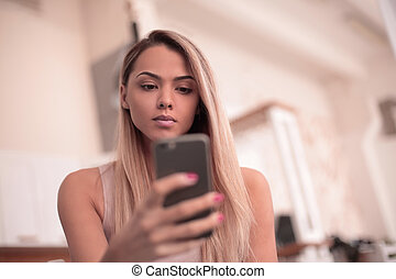 close up. serious young woman reading SMS on her smartphone