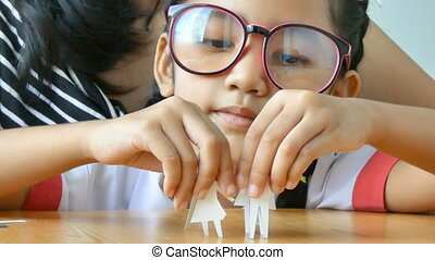 Close up shot Asian little girl in Thai kindergarten student uniform and her mother playing cut of white paper making family shape father mother son and daughter on wooden table
