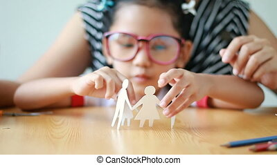 Close up shot Asian little girl in Thai kindergarten student uniform and her mother playing cut of white paper making family shape father mother son and daughter on wooden table select focus shallow depth of field