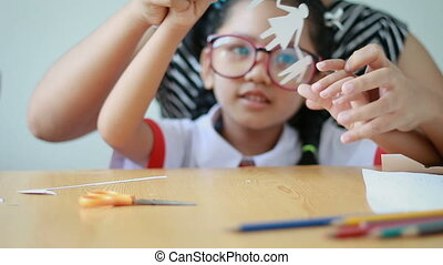 Close up shot Asian little girl in Thai kindergarten student uniform and her mother playing cut of white paper making family shape father mother son and daughter on wooden table select focus on hands