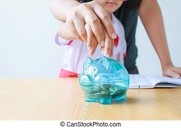 Close up shot Asian little girl in Thai student kindergarten uniform with mother hand putting money coin into clear piggy bank shallow depth of field select focus on pig