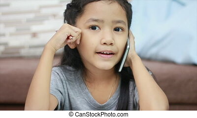 Close up shot Asian little girl using pencil doing homework and talk to smartphone