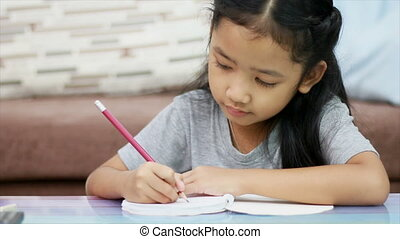 Close up shot Asian little girl using pencil write to a note book doing homework with concentration for home school and education concept