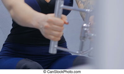 Close up shot. Athletic young woman working out on fitness exercise equipment