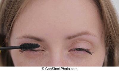 Close up shot - beautiful young woman putting mascara. White...