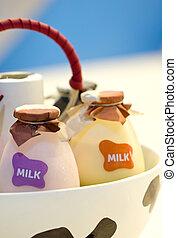 Close up shot bottles of milk in basket.