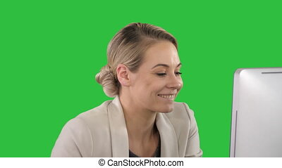 Elegant businesswoman cheering at office desk looking at monitor on a Green Screen, Chroma Key.