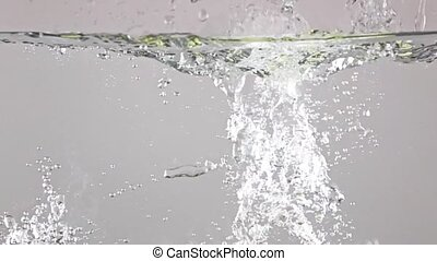 Close up shot: green apples fall in water, gray background, super slow motion