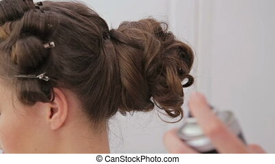 Close up shot. Hair stylist, hairdresser finishing hairstyle for young woman