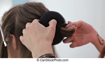 Close up shot. Hairdresser doing hairstyle for young pretty woman with long hair