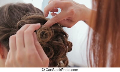 Close up shot. Hairdresser finishing hairstyle for young pretty woman