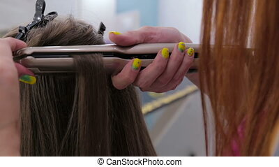 Close up shot. Hairdresser using straightener on long hair of client