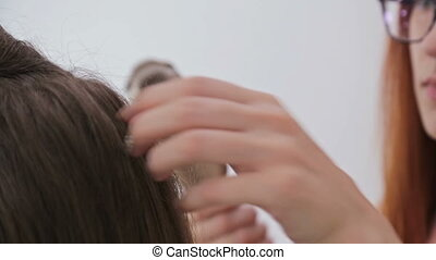 Close up shot. Hairdresser using straightener on long woman hair in hair salon