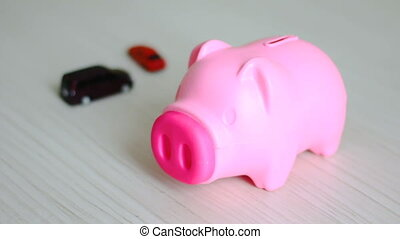 Close up shot hand of man putting money coin into pink piggy bank and blur car behind metaphor of saving money for buy the car concept