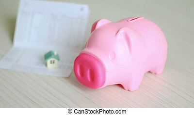 Close up shot hand of man putting money coin into pink piggy bank and blur home and book bank passbook behind metaphor of saving money for buy the home concept