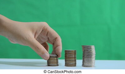 Close up shot hand of woman removing stack of the coins over green background