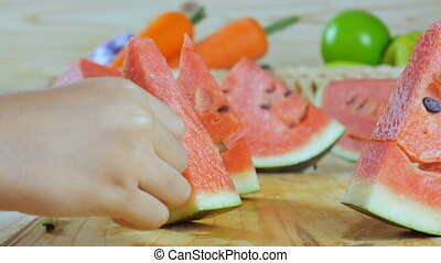 Close up shot hands making smile face a cut piece of ripe watermelon on wooden cut board fresh fruit for summer