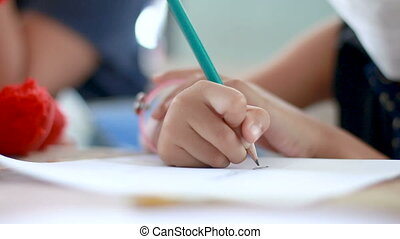 Close up shot hands of girl drawing with pencil shallow...