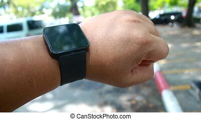 Close up shot hands of man using smart watch in car parking...