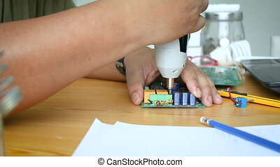 Close up shot hands of mechanic man using electric screwdriver to spin the screw on electronic print circuit board with ambient sound