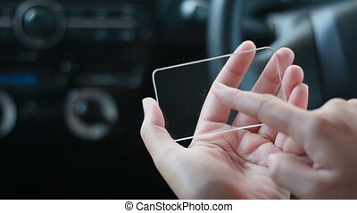 Close up shot hands of woman using clear glass smart phone...