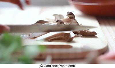 Close up shot hands of woman using kitchen knife slide cut Eringi mushroom preparing for cooking
