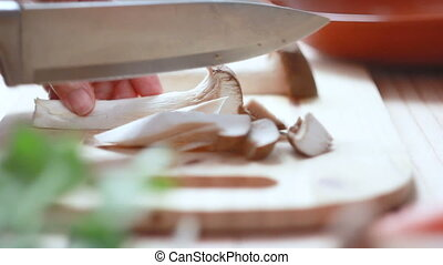 Close up shot hands of woman using kitchen knife slide cut Eringi mushroom preparing for cooking