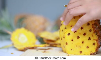 Close up shot hands of women using kitchen knife to cutting and peeling ripe pineapple shallow depth of field with ambient sound
