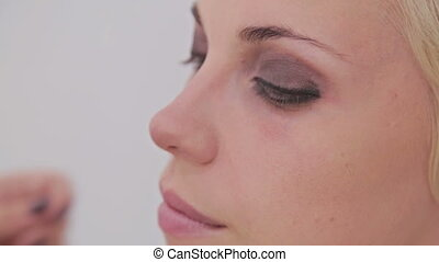 Close up shot. Make-up artist applying eyeliner around the...