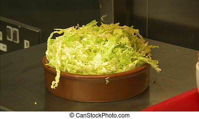 Close up shot of a bowl of cut lettuce, in a metal...