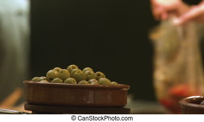 Close up shot of a bowl of olives as people work - Close up...