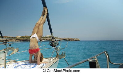 Close-up Shot of a Fit Young Woman Doing Yoga on a Sailing Yacht. In the Background Beautiful Calm Sea and Clear Sunny Sky